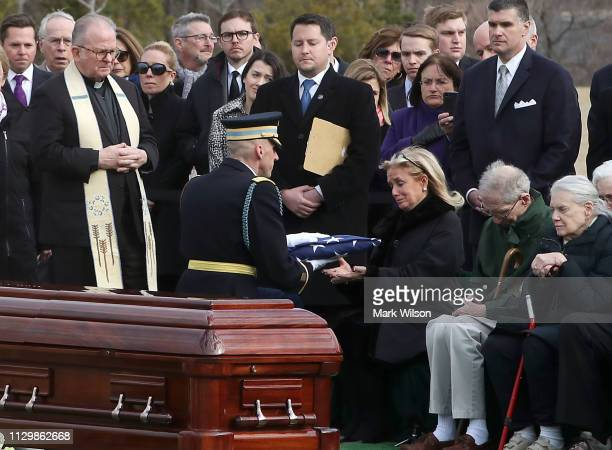 Debbie Dingell receives the flag that covered the casket of her husband former Rep. John Dingell during a funeral service at Arlington National...