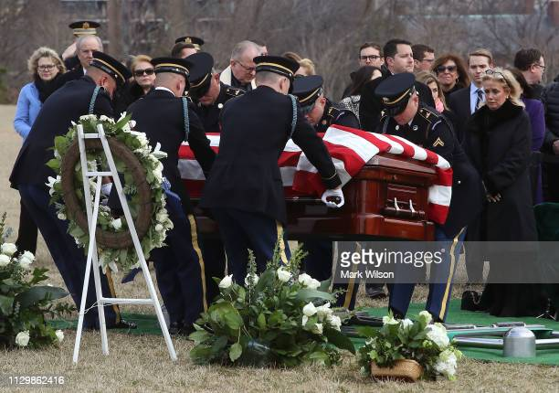 Debbie Dingell watches as the casket carrying the remains of her husband former Rep. John Dingell is lowered during a funeral service at Arlington...