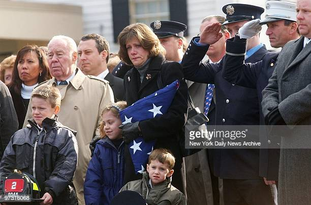 Debbie Harlin widow of Firefighter Daniel Edward Harlin clasps flag as she mourns with children Christopher Katie and Brian during memorial service...