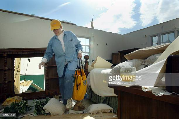 Debbie Jacques steps over debris in her bedroom while looking personal belongings on the morning after a tornado tore the roof off of her house April...