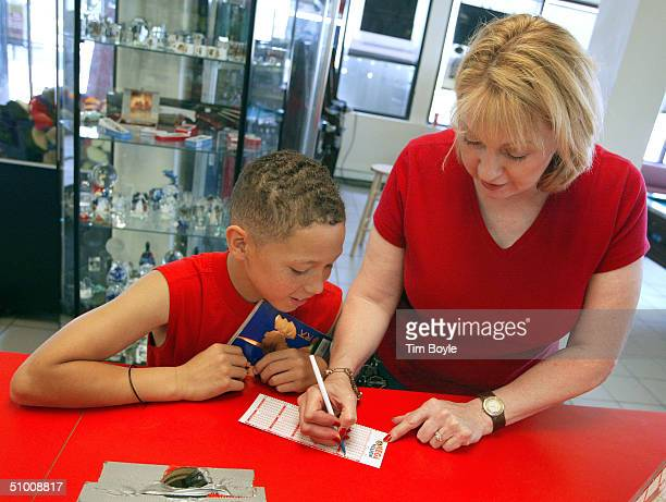 Debbie Nash from Kenosha Wisconsin fills out her Mega Millions lottery ticket as her son Jerry Nash looks on June 29 2004 at a Citgo gas station in...
