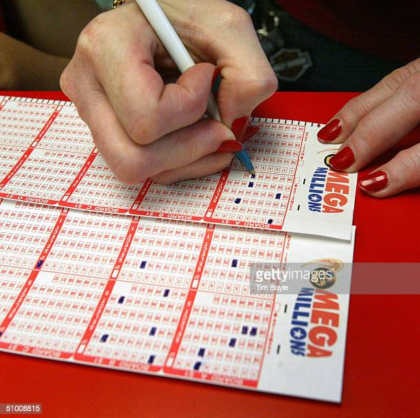 Debbie Nash from Kenosha Wisconsin fills out her Mega Millions lottery ticket June 29 2004 at a Citgo gas station in Russell Illinois on the border...