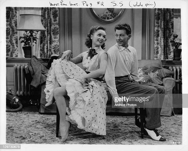 Debbie Reynolds and Donald O'Connor sitting back to back in a scene from the film 'I Love Melvin' 1953