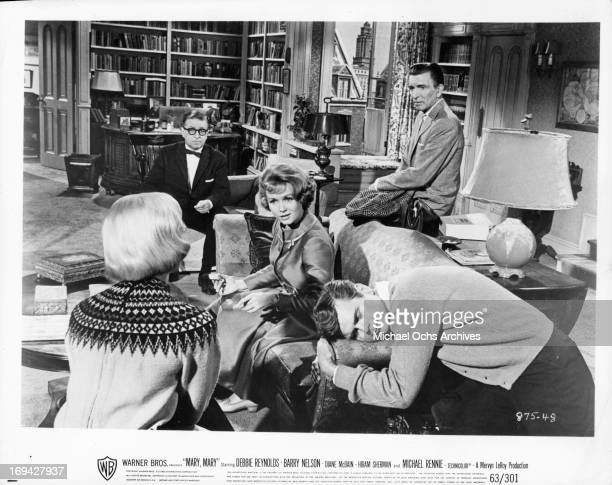Debbie Reynolds, Barry Nelson, and Michael Rennie gathered around couch in a scene from the film 'Mary, Mary', 1963.