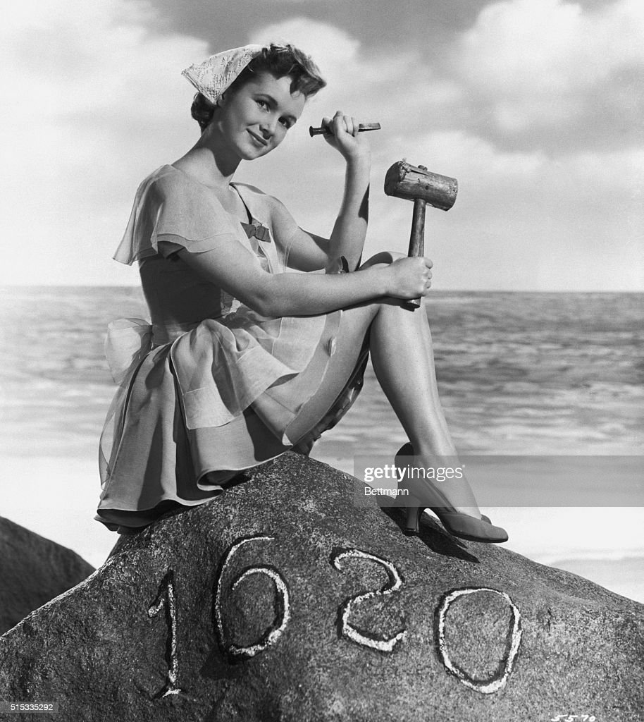 Debbie Reynolds, dressed as a pilgrim, sits on top of a replica of Plymouth Rock holding a mallet and a chisel.