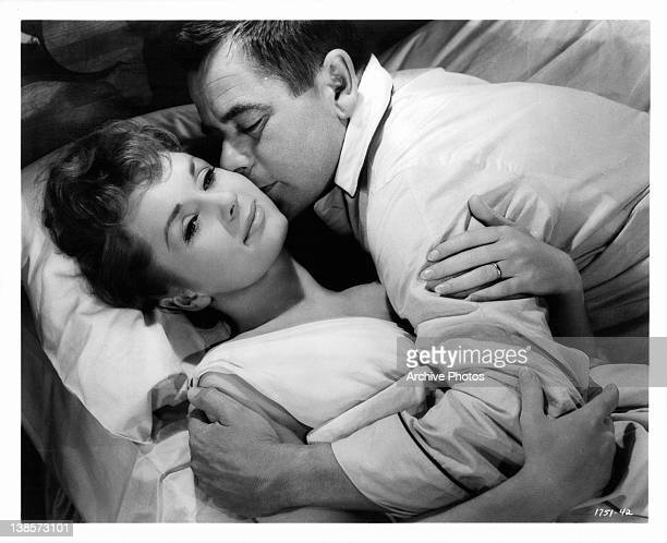 Debbie Reynolds holding arm of Glenn Ford as he kisses her cheek in a scene from the film 'It Started With A Kiss' 1959