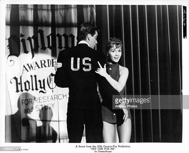 Debbie Reynolds in a very short dress with her hands on an unknown actor's arms in a scene from the film 'Say One For Me' 1959
