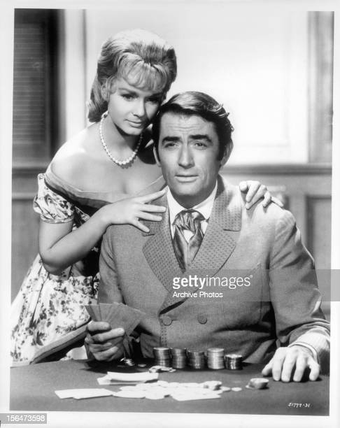 Debbie Reynolds looks over Gregory Peck's shoulder as he is gambles in a scene from the film 'How The West Was Won' 1962