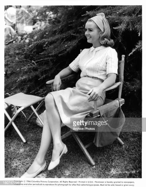 Debbie Reynolds relaxing in a chair outside in a yard in a scene from the film 'Divorce American Style' 1967