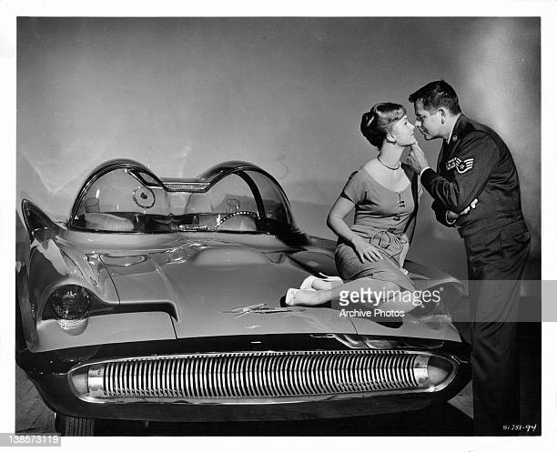 Debbie Reynolds sits on hood of car as Glenn Ford holds her chin and they lean in to kiss in a scene from the film 'It Started With A Kiss' 1959