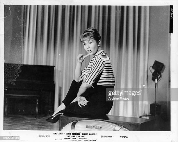 Debbie Reynolds sitting on a speaker on a stage with her finger on her cheek in a scene from the film 'Say One For Me' 1959