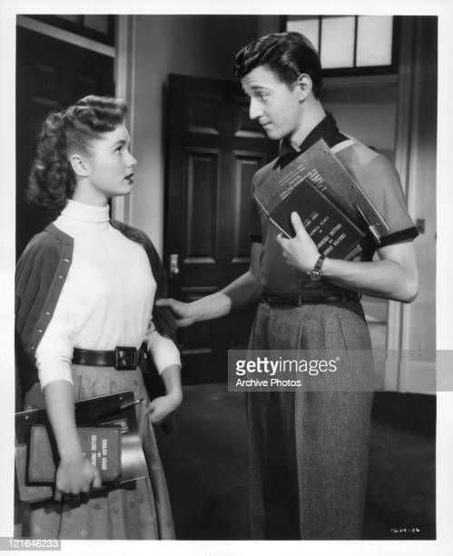 Debbie Reynolds stands hold books while Bobby Van pulls on her arm in a scene from the film 'Affairs Of Dobie Gillis' 1953