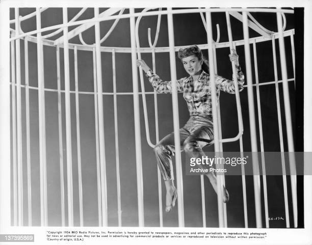 Debbie Reynolds swinging in birdcage in dream sequence scene from the film 'Susan Slept Here' 1954
