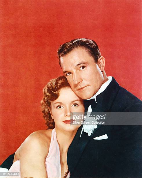 Debbie Reynolds US actress singer and dancer poses with Gene Kelly US actor singer and dancer in a studio portrait against a red background issued as...