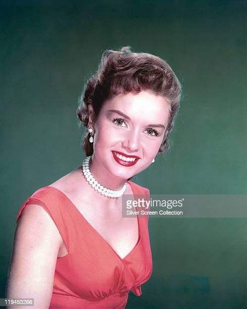 Debbie Reynolds US actress singer and dancer wearing a red sleeveless top and a white pearl necklace in a studio portrait against a green background...