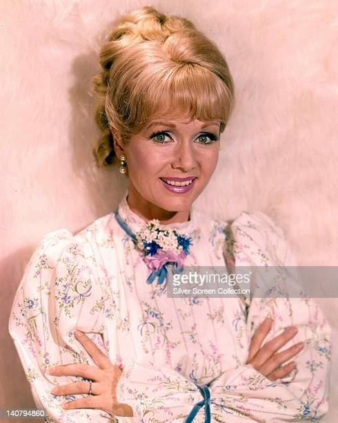 Debbie Reynolds US actress singer and dancer wearing a white long sleeve top with floral motifs blue ribbons at the neck and around the cuffs smiling...