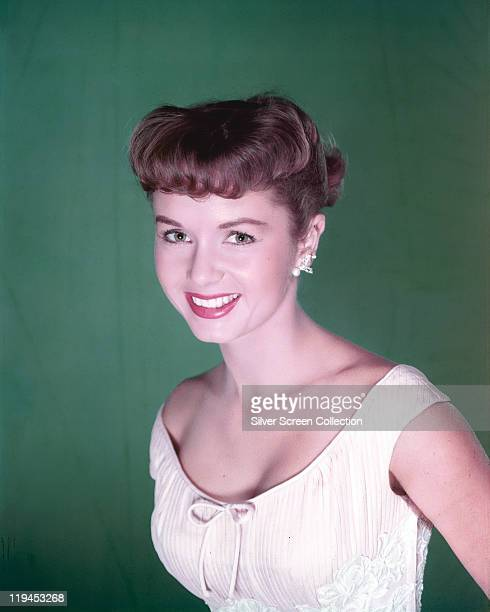 Debbie Reynolds US actress singer and dancer wearing a white sleeveless top in a studio portrait against a green background circa 1955