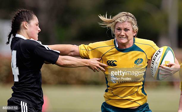 Debby Hodgkinson of the Wallaroos fends off a tackle by Victoria Blackledge of the Black Ferns during the second test match between the Australian...