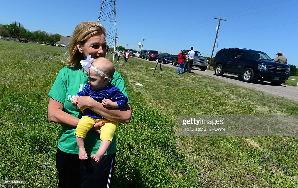 Debby Keel holds her grandchild Kennedy near where Texas Highway Patrol officers take down details and mark the vehicles of residents being allowed to return to their destroyed homes near the site of the April 17 fertilizer plant blast in West, Texas, on April 20, 2013. Investigators have been treating the blast site as a crime scene, although authorities say the blast was likely caused by a fire at the West Fertilizer Company, and access to the area has been restricted until today with residents allowed to return. Debby's home near the Intermediate school was among those destroyed but she was not home at the time, and though her husband was, he survived with injuries resulting in some forty stitches. AFP PHOTO/Frederic J. BROWN