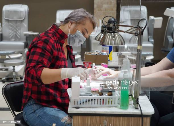 Debi Dang works on the nails of a customer at Allure Nail Bar in Atlanta, Georgia on April 24, 2020. - Governor Brian Kemp has eased restrictions...