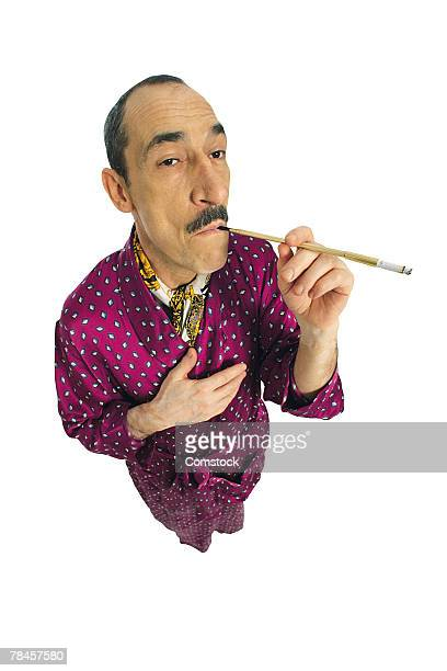 debonair man smoking cigarette - smoking jacket stock photos and pictures