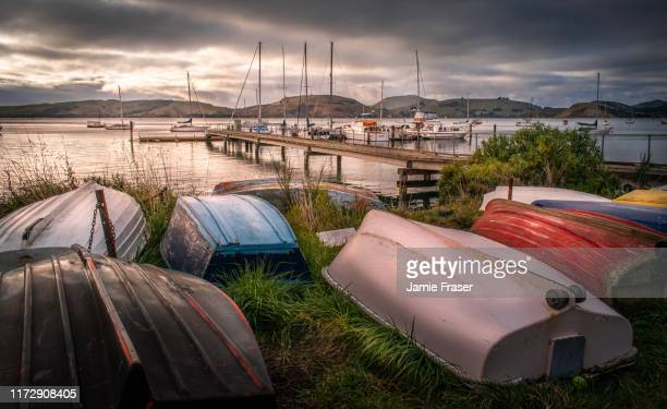 deborah bay, dunedin new zealand pier and tender dinghies on moody day - dunedin new zealand stock pictures, royalty-free photos & images