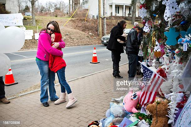 Deborah Gibelli holds her daughter Alexandra Gibelli age 9 while looking at a memorial for those killed in the school shooting at Sandy Hook...