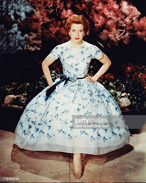 Deborah Kerr British actress wearing a white dress with blue floral motifs tied around the waist with a blue ribbon in a studio portrait sitting in a...