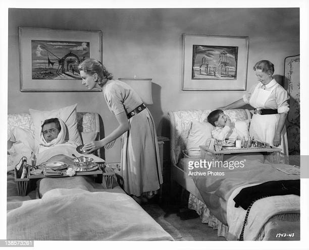 Deborah Kerr nurses Rossano Brazzi back to health from the measles as Mona Washbourne does the same with Martin Stephens in a scene from the film...