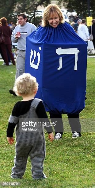 Deborah Leshon dressed up as a dreidel entertains a visitor to the Conejo Valley Hanukkah Festival in Thousand Oaks