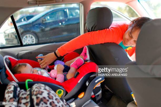 Deborah Oquendo fastens the seatbelt of the car seat of her 10mo old daughter Genesis Rivera in Orlando Florida on December 1 2017 On September 20...
