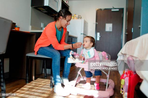 Deborah Oquendo gives breakfast to her 10mo old daughter Genesis Rivera at the hotel were they are staying in Orlando Florida on December 1 2017 On...
