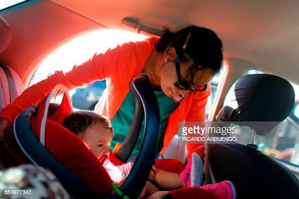 Deborah Oquendo removes from her car her 10mo old daughter Genesis Rivera in her carseat in Orlando Florida on December 1 2017 On September 20...