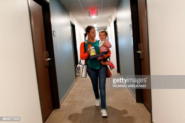 Deborah Oquendo walks carrying her 10mo old daughter Genesis Rivera at the hotel were they are staying in Orlando Florida on December 1 2017 On...