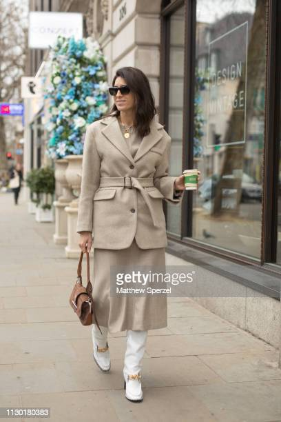 Deborah Reyner Sebag is seen on the street during London Fashion Week February 2019 wearing taupe coat sweater and skirt with white shoes on February...