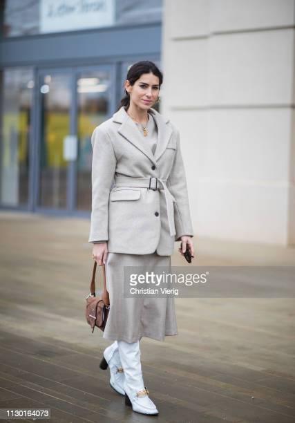 Deborah Reyner Sebag is seen wearing brown Prada bag white boots grey belted jacket skirt outside ALEXACHUNG during London Fashion Week February 2019...