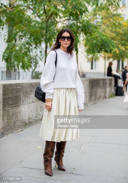 Deborah Reyner Sebag is seen wearing creme white pleated skirt jumper black bag brown boots with snake print outside Paco Rabanne during Paris...