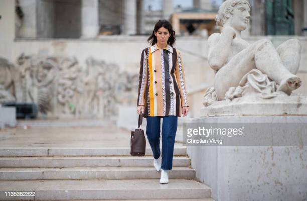 Deborah Reyner Sebag is seen wearing dark blue denim jeans brown bag white ankle boots striped butto shirt outside Tods lunch during Paris Fashion...