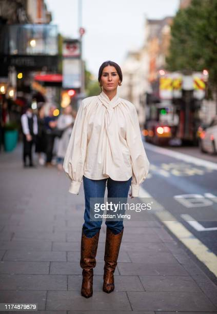 Deborah Reyner Sebag is seen wearing denim jeans creme white blouse brown boots outside AWAKE during London Fashion Week September 2019 on September...