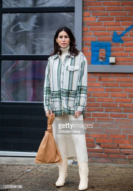 Deborah Reyner Sebag seen wearing striped jacket, brown Bottega Veneta the twist bag, skirt, boots outside Holzweiler during Copenhagen Fashion Week...