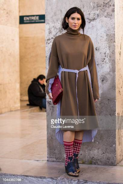 Deborah Reyner Sebag wearing a beige knitted dress decorated boots and red Gucci bag is seen before the Sacai show on October 1 2018 in Paris France