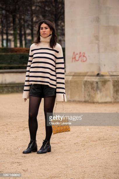 Deborah Reyner Sebag wearing a black and white jumper black mini leather skirt black shoes and tan bag is seen in the streets of Paris after the...