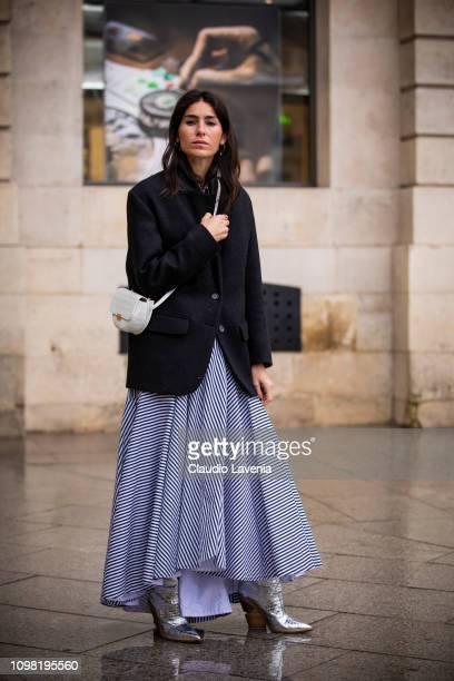 Deborah Reyner Sebag, wearing a dark blue blazer, long striped skirt, silver boots and white bag, is seen outside Alexis Mabille show during Paris...