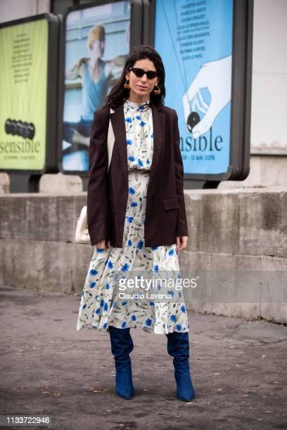 Deborah Reyner Sebag wearing a long printed white dress blue boots cream bag and brown blazer is seen outside Sacai on Day 8 Paris Fashion Week...