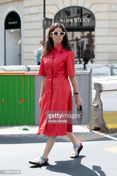 Deborah Reyner Sebag wears a Dior bag white Gucci sunglasses Arizona Love sandals and a red leather dress on July 01 2019 in Paris France