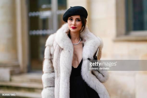 Deborah Valdez Hung wears a beret hat a white fur coat a black dress after Dior during Haute Couture Spring/Summer 2018 on January 22 2018 in Paris...