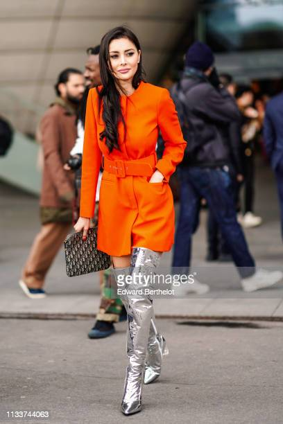 Deborah Valdez-Hung wears a red dress, shiny silver thigh high boots, a Dior monogram bag, outside Giambattista Valli, during Paris Fashion Week...