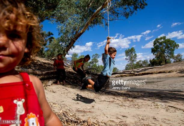 Deborah Whyman swings from a tree over the dry bed of the Darling -Barka river as other family members play on March 04, 2019 in Wilcannia,...
