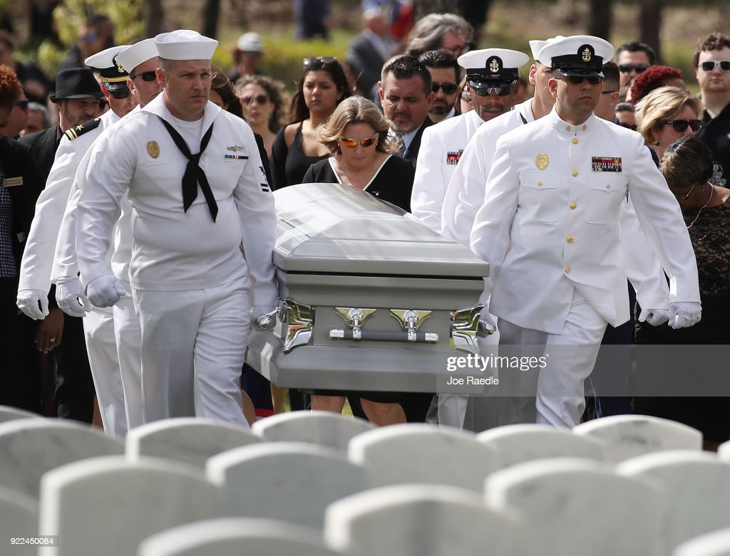 Debra Hixon (C) follows the Naval Security Force Key West pallbearers as they carry the casket of her husband Chris Hixon, who was the athletic director, at Marjory Stoneman Douglas High School for his burial at South Florida National Cemetery on February 21, 2018 in Lake Worth, Florida. Police arrested 19 year old former student Nikolas Cruz for the killing of 17 people at the high school on February 14.
