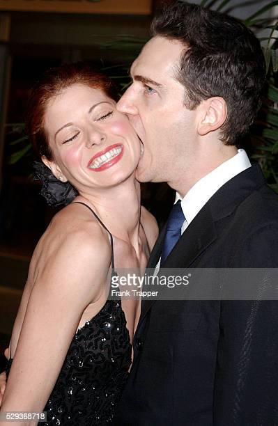 Debra Messing is given a biting kiss on her cheek by her husband at the Fulfillment Fund Stars 2001 Benefit Gala honoring Jeffrey Katzenberg